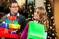 Couple with Christmas presents and bags in shoppin Royalty Free Stock Images