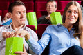 Couple in cinema theater with popcorn watching a movie they eating Royalty Free Stock Image