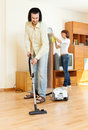 Couple cleaning with vacuum cleaner Royalty Free Stock Photo