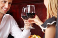 Couple clinking glasses of red wine happy in a restaurant Stock Photo