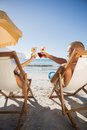 Couple clinking their glasses while relaxing on their deck chair the beach chairs Stock Photography