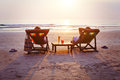 Couple with cocktails relaxing on the beach Royalty Free Stock Photo
