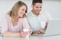 Couple with coffee mugs using laptop at table smiling young in kitchen Royalty Free Stock Photo