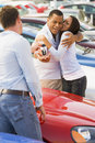 Couple collecting new car from salesman Royalty Free Stock Image