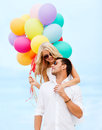 Couple with colorful balloons at seaside summer holidays celebration and dating concept Stock Photo