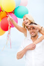 Couple with colorful balloons at seaside summer holidays celebration and dating concept Royalty Free Stock Images
