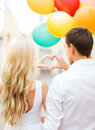 Couple with colorful balloons summer holidays celebration and dating concept making heart shape in the city Stock Photography
