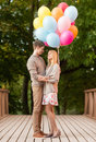 Couple with colorful balloons summer holidays celebration and dating concept in the park Royalty Free Stock Images