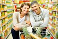 Couple of consumers image happy with cart looking at camera in supermarket Royalty Free Stock Photo