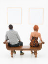 Couple contemplating art rear view of men an women sitting on a wooden bench looking at empty frames displayed on a white wall in Royalty Free Stock Photography