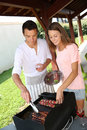 Couple cooking on barbecue meat grill at home Royalty Free Stock Photos