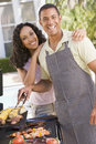 Couple Cooking On A Barbeque Royalty Free Stock Image