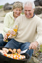 Couple Cooking Barbeque On A Beach Royalty Free Stock Image