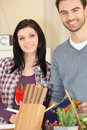Couple cooking meal from recipe Stock Photography