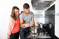 Couple cooking a meal on stove young in domestic kitchen Royalty Free Stock Photo