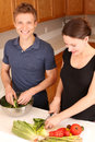 Couple cooking young in the kitchen together Royalty Free Stock Photos