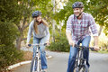 Couple on cycle ride in countryside smiling Stock Image