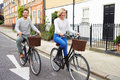 Couple cycling along urban street together with basket on bike Royalty Free Stock Photography