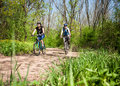 Couple cycling in spring forest Royalty Free Stock Image