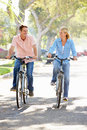 Couple cycling on suburban street smiling to each other Stock Images