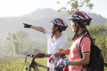 Couple cyclist portrait of two happy asian bikers pointing at the forest Stock Photo