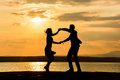 A couple dancing by the sea at sunset Royalty Free Stock Photo