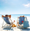 Couple on a deck chair relaxing on the beach Royalty Free Stock Images