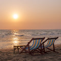 A couple of deck chairs on beach the sand sea sunset Royalty Free Stock Images