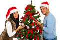 Couple decorate christmas tree chistmas together and smiling to camera Royalty Free Stock Images