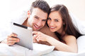 Couple with digital tablet in bed using Royalty Free Stock Image