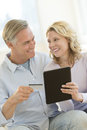 Couple with digital tablet and credit card shopping online happy mature looking at each other while Royalty Free Stock Photo