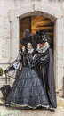 Couple disguised annecy france march a in black costumes poses in front of the entrance in a stones building during the annecy Royalty Free Stock Image