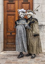 Couple disguised annecy france march a poses near a wooden gate during the annecy venetian carnival yearly in annecy france is Stock Images