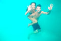 Couple diving underwater a young in a blue clean water and waving towards camera Stock Photos