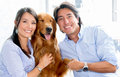 Couple with a dog happy holding their Royalty Free Stock Photography
