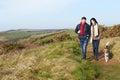 Couple With Dog Walking Along Coastal Path Royalty Free Stock Photo