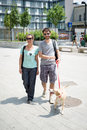 Couple with dog walking in the street morning Stock Photos