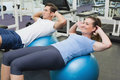 Couple doing sit ups on exercise balls Royalty Free Stock Photo