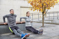 Couple doing triceps dip on city street bench Royalty Free Stock Photo