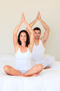Couple doing yoga in bed Royalty Free Stock Photography