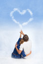 Couple drawing heart in the sky young sitting on clouds over blue Stock Photos