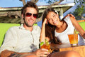 Couple drinking alcohol at beach club having fun with alcoholic drink beverage mai tai cocktail on hawaii portrait of romantic Stock Images