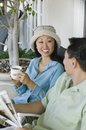 Couple drinking coffee and reading newspaper outdoors Stock Photos
