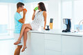 Couple drinking coffee and spending time together in the kitchen happy young women is sitting on worktop her boyfriend is Royalty Free Stock Images