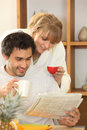 Couple drinking coffee together and looking at a newspaper Royalty Free Stock Photos