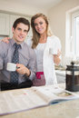 Couple drinking coffee together while reading newspaper in kitchen Royalty Free Stock Photos