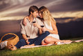 Couple drinking glass of wine on romantic sunset picnic attractive Royalty Free Stock Images