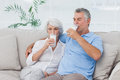 Couple drinking glasses of milk sitting on the couch mature Stock Image