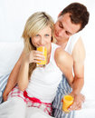 Couple drinking orange juice in bed Royalty Free Stock Photos