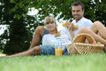 Couple drinking orange juice in a park Royalty Free Stock Photos